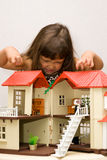 Girl and house for dolls. The little girl has become angry with a small house for dolls Stock Photography
