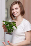 Girl with houseplant Stock Image