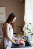 Girl housewife washes dirty dishes in the kitchen. 1 Royalty Free Stock Photo