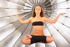 Girl hovers in air in yoga posture in studio Royalty Free Stock Photography
