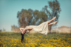Girl hovers over the field. Girl floating in weightlessness over the meadow of dandelions Stock Photo
