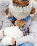 Girl hug warming her dog in cold day stock photo