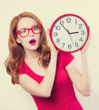Girl with huge clock. Surprised redhead girl with huge alarm clock on light background Stock Photography