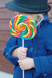 Girl and huge lollypop. Girl holding big rainbow lollypop turning her face to the left stock photos