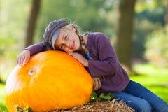 Girl with huge pumpkin Stock Images