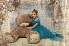 Girl with huge teddybear. Girl in a turquoise dress with huge teddybear Royalty Free Stock Photos