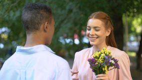 Girl hugging Afro-American boyfriend after presenting bunch of flowers, date. Stock footage stock footage