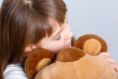 Girl hugging bear. A portrait of a young pretty girl smiling and hugging her teddy bear Royalty Free Stock Photography