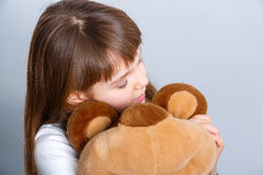 Girl hugging bear. A portrait of a young pretty girl smiling and hugging her teddy bear Royalty Free Stock Photo