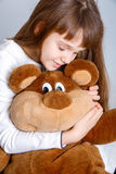 Girl hugging bear. A portrait of a young pretty girl smiling and hugging her teddy bear Royalty Free Stock Image