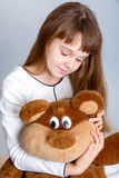 Girl hugging bear. A portrait of a young pretty girl smiling and hugging her teddy bear Stock Photography