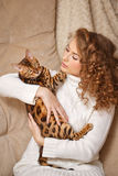 Girl hugging Bengal cat. Royalty Free Stock Images