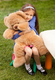 Girl hugging big teddy bear while sitting on chair at yard Royalty Free Stock Photos