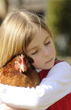 Girl hugging a chicken Stock Images