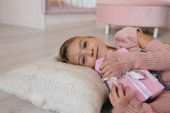 girl hugging a Christmas gift box. smiling kid lying on a pillow and holding a present Stock Image