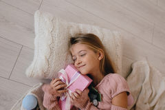 Girl hugging a Christmas gift box. smiling kid lying on a pillow and holding a present Stock Images