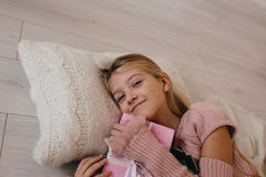 Girl hugging a Christmas gift box. smiling kid lying on a pillow and holding a present Royalty Free Stock Image