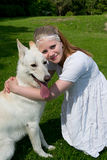 Girl hugging a dog. Girl hugging a white shepherd dog sitting on a lawn Royalty Free Stock Image