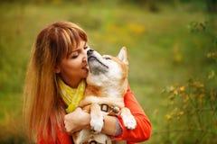 Girl hugging dog Shiba Inu in autumn park. stock photos
