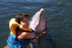 Girl is hugging a dolphin Stock Images