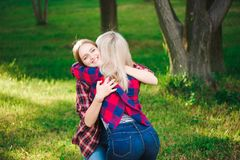 Girl hugging her best friend in the park stock photos