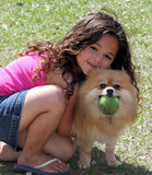 Girl hugging her dog. Young girl hugging and playing fetch with her dog stock photos
