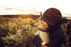 Girl hugging her dog in the field with a sunset royalty free stock photo