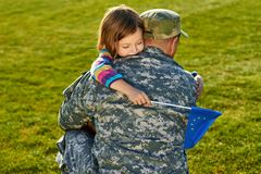 Girl is hugging her father EU soldier. stock photo