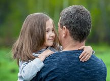 Girl hugging her father. Happy loving family. Dad and his daughter playing. Cute baby and daddy. Concept of Father day. Family holiday and togetherness. Green stock images