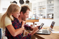 Girl hugging her father, working on laptop at home Royalty Free Stock Image
