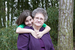 Girl hugging her Great Grandmother. Beautiful little brunette girl hugging her Great Grandmother in outdoor wooded setting Royalty Free Stock Image