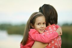 Girl hugging her mother Royalty Free Stock Image