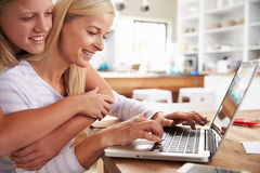 Girl hugging her mother, working on laptop at home Stock Images
