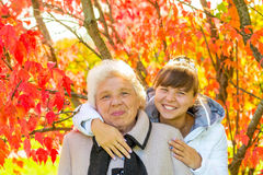 Girl hugging her old grandmother in park Stock Image