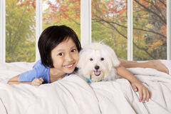 Girl hugging her puppy on the bed. Image of happy little girl smiling at the camera while hugging her puppy and lying on the bed with autumn background on the Royalty Free Stock Images