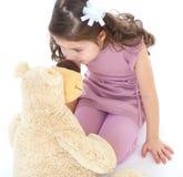 Girl hugging her teddy bear. Stock Photos