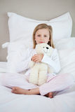 Girl hugging her teddy on the bed Royalty Free Stock Images
