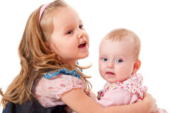 Girl hugging her younger sister Royalty Free Stock Images