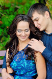 Girl hugging his boyfriend, both looking at the cam and smiling Stock Photos