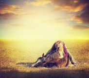 Girl hugging a horse and lying on grass over background of pasture with sunset sky Royalty Free Stock Photography