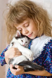 Girl hugging a kitten Royalty Free Stock Images