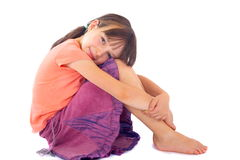 Girl hugging knees to chest Stock Photo