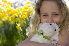 Girl hugging lamb toy in flowers stock photography
