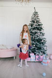 Girl hugging little sister near a Christmas tree and gift boxes Royalty Free Stock Image