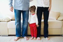 Girl hugging mom and dad for legs Royalty Free Stock Photos