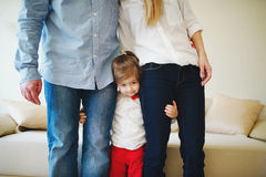 Girl hugging mom and dad for legs Stock Images