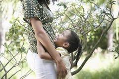 Girl Hugging Mother In Garden Stock Images