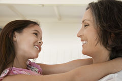 Girl Hugging Mother At Home Stock Image