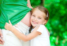 Girl hugging mother's belly Royalty Free Stock Images