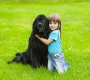 Girl hugging Newfoundland dog Royalty Free Stock Photos